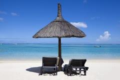 Miesiąca miodowego o tropikalna wyspa Mauritius, sunbeds z palmowym liściem pokrywa strzechą dekarstwo parasole Fotografia Stock