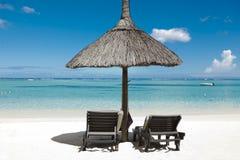 Miesiąca miodowego o tropikalna wyspa Mauritius, sunbeds z palmowym liściem pokrywa strzechą dekarstwo parasole Zdjęcie Stock