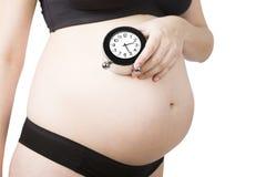4 miesięcy kobieta w ciąży na sport bielizny mienia budziku fotografia royalty free