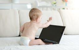 10 miesięcy starej chłopiec siedzi na kanapie i ma wideokonferencja na laptopie w pieluszkach Ty możesz wkładać twój wizerunek da Zdjęcie Royalty Free