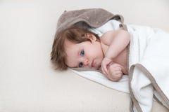 3 miesięcy stary dziecko zawijający w ręczniku na białym tle patrzeje ciebie szczęśliwy dzieciństwa pojęcie Obrazy Royalty Free