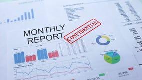 Miesięczny raport poufny, ręki cechowania foka na urzędowym dokumencie, statystyki zbiory