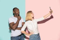 Mieszana ścigająca się para ucznie bierze pospolitego selfie z telefonem Kaukaska dziewczyna i jej Afrykański chłopak pozuje przy fotografia royalty free