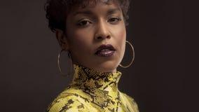 Mieszana biegowa amerykanin afrykańskiego pochodzenia kobieta w jaskrawej kolor żółty sukni z pytonu drukiem 90 ` s styl zbiory