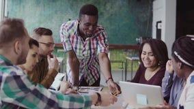 Mieszana biegowa grupa architekci na biznesowym spotkaniu w nowożytnym biurze Męski afrykański lider zespołu dyskutuje pomysły