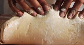 Mieszana biegowa mężczyzna ` s ręka ugniata ciasto na drewnie i robi piłce od go zbiory