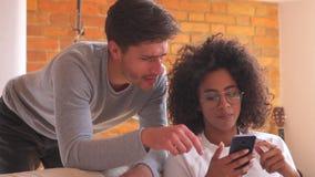 Mieszana biegowa para używa telefon komórkowego w żywym pokoju w domu zbiory wideo