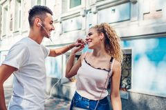 Mieszana biegowa para w miłości słucha muzyka na telefonie i tanu na miasto ulicie używać słuchawkę obrazy stock