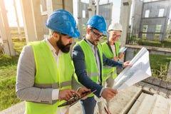 Mieszana grupa młodzi architekci, cywilni inżyniery i partnery biznesowi spotyka na wielkiej budowie obrazy stock