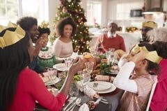 Mieszana rasa, wielo- pokolenia rodzinny obsiadanie przy Bożenarodzeniowym obiadowego stołu czytaniem żartuje i będący ubranym pa zdjęcie stock