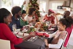 Mieszana rasa, wielo- pokolenie rodzina ma zabawy ciągnięcia krakersy przy Bożenarodzeniowym obiadowym stołem obraz royalty free