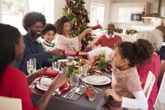 Mieszana rasa, wielo- pokolenie rodzina ma zabawy ciągnięcia krakersy przy Bożenarodzeniowym obiadowym stołem zdjęcia stock