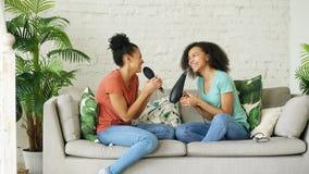 Mieszane biegowe młode śmieszne dziewczyny tanczą śpiew z hairdryer i grępli obsiadaniem na kanapie Siostry ma zabawa czas wolneg Obrazy Stock