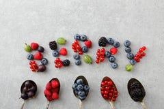 Mieszane jagody w starych łyżkach i kształtować jako list Obrazy Royalty Free
