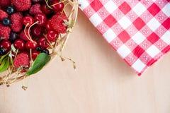 Mieszane lato jagody w koszu na stole Fotografia Stock