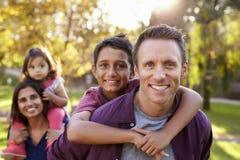 Mieszani biegowi rodzice niosą dzieciaków piggyback, selekcyjna ostrość Fotografia Royalty Free