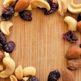 Mieszani owoc i dokrętki na drewna adry tnącej desce, ustawiona w kwadratowym wizerunku dla ogólnospołecznych środków, sztandarów Fotografia Stock
