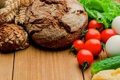 Mieszani warzywa i dwa chleba na kuchennym stole zdjęcie royalty free