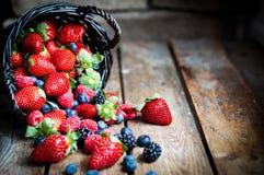 Mieszanka świeże jagody w koszu na nieociosanym drewnianym tle Zdjęcia Stock
