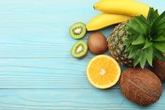 mieszanka świeży koks, banan, kiwi owoc, pomarańcze i ananas na błękitnym drewnianym tle, Odgórny widok z kopii przestrzenią fotografia royalty free