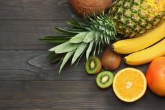 mieszanka świeży koks, banan, kiwi owoc, pomarańcze i ananas na ciemnym drewnianym tle, Odgórny widok z kopii przestrzenią fotografia royalty free