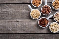 Mieszanka dokrętek pistacje, migdały, orzechy włoscy, sosnowa dokrętka, hazelnuts i nerkodrzew, Przekąska w pucharu backgrond fotografia stock