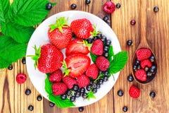 Mieszanka jagody w talerzu i łyżka na drewnianym tle świeże, dojrzałe, odgórny widok Fotografia Stock