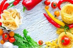 Mieszanka makaron, pomidory i chili kopia, interliniujemy nieociosanego drewnianego backgr fotografia stock