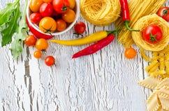 Mieszanka makaron, pomidory i chili kopii przestrzeni drewniany tło, obraz stock