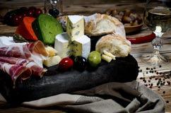 Mieszanka ser na ciemnym tle na drewno desce z winogronami, miodem, dokr?tkami, pomidorami i basilem, Odg?rny widok obraz stock