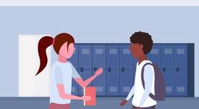 Mieszanka uczni biegowa para dyskutuje w szkoła lobby korytarza wnętrzu z rzędem błękitna szafki komunikacji edukacja royalty ilustracja