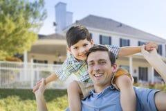 Mieszany Biegowy ojca i syna Piggyback przed domem fotografia royalty free