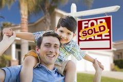 Mieszany Biegowy ojciec, syna Piggyback, przód dom, Sprzedający znak Zdjęcia Stock