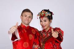 Mieszany Biegowy państwo młodzi jest ubranym tradycyjnych chińskie ślubnych stroje w studiu zdjęcia royalty free