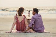Mieszany biegowy rodzinny mieć odpoczynek na plaży zdjęcia stock
