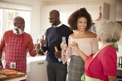 Mieszany biegowy senior i potomstwo dorosłej rodzinnej podwyżki szampańscy szkła świętować, podczas gdy przygotowywający Bożenaro obrazy stock