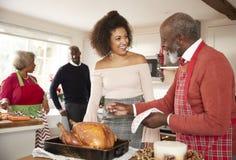 Mieszany biegowy senior i potomstwo dorosli członkowie rodzini opowiada w kuchni podczas gdy przygotowywający Bożenarodzeniowego  obraz royalty free