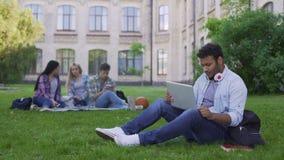 Mieszany biegowy studencki gawędzenie online na laptopie, siedzi na trawie blisko uniwersyteta zbiory wideo