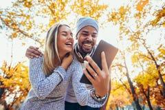 Mieszany pary odprowadzenie w jesień parku, używać cyfrową zakładkę obraz stock