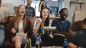 Mieszany pochodzenie etniczne grupy dopatrywanie bawi się grę na TV Emocjonalni fan na leżance z napojów i przekąsek 4K zwolnione zdjęcia stock