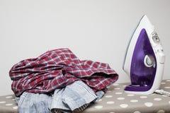 Mieszkania żelazo i czyści odzieżowego na desce fotografia stock