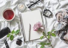 Mieszkania piękna produktów nieatutowy tło Notepad, róża, pachnidło, tusz do rzęs, zegarki, szkła, hełmofony, telefon, szalik i h obraz stock