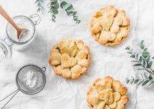 Mieszkania shortcrust nieatutowego crispy ciasta jabłczani tartlets na lekkim tle, odgórny widok Walentynki ` s dnia pieczenie Obrazy Royalty Free