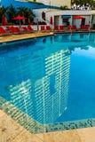 Mieszkania własnościowego wierza Odbijający w Błękitnym basenie Zdjęcia Royalty Free