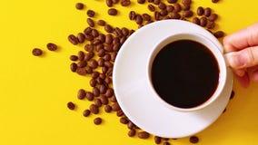 Mieszkanie nieatutowa żeńska ręka bierze szklanego filiżanka kawy od koloru żółtego stołu Ranku czas, budzi się zbiory