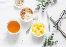 Mieszkanie nieatutowego ranku śniadaniowa inspiracja - grecki jogurt z całymi zbożowymi zbożami, herbatą, ananasem i notepad, szk Fotografia Stock