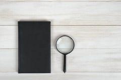 Mieszkanie nieatutowy czarny notatnik i powiększać - szkło na lekkiej drewnianej powierzchni Obraz Royalty Free