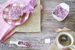 Mieszkanie nieatutowy, Holenderski śniadanie z rusk, filiżanka herbata, różowy cukierki kropi przeciw drewnianemu tłu, grad na ta obraz stock