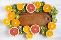 Mieszkanie nieatutowy Odgórny widok Drewniana deska w centrum z pokrojonym kiwi, pomarańcze, grapefruitowym, i mandarynka na lekk obraz royalty free