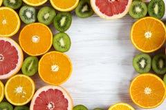 Mieszkanie nieatutowy Odgórny widok Odbitkowa przestrzeń z pokrojonym kiwi, pomarańcze, grapefruitowym, i mandarynka na lekkim dr fotografia stock